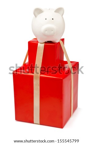 Savings and gifts. Stack of gift boxes with piggy bank above