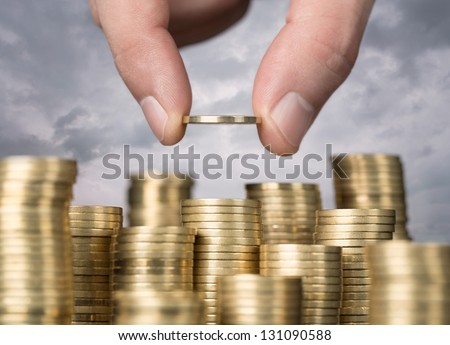 Savings, close up of male hand stacking golden coins over sky background