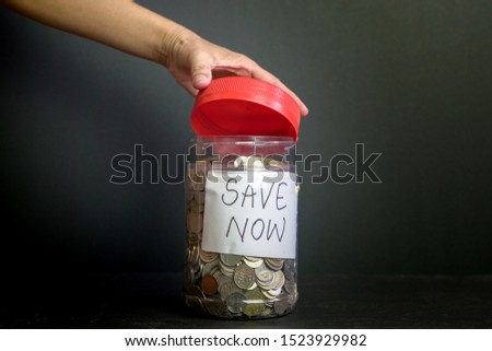 Savings concept. Coins saved inside container with Save Now words written on paper.