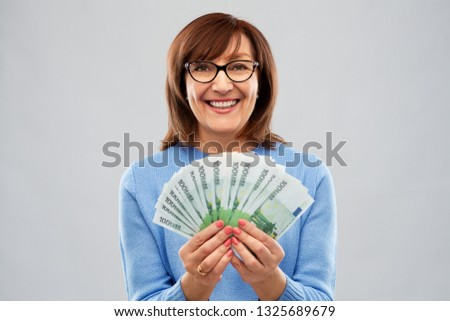 savings, finances and people concept - smiling senior woman holding hundred euro money banknotes