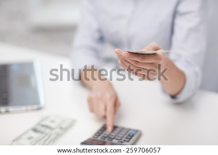 savings, finances, economy, technology and people concept - close up of woman counting money with calculator