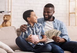 Savings For Education. Happy Black Father And Son Sitting On Couch With Dollar Cash Money And Piggybank, Free Space
