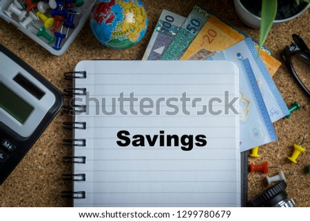 SAVINGS inscription written on book with globe,eyeglasses, calculator, camera, pencil and vase on wooden background with selective focus and crop fragment. Business and education concept Stock fotó ©