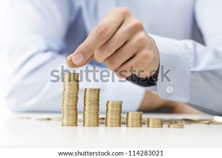 Savings, male hand stacking gold coins into increasing columns