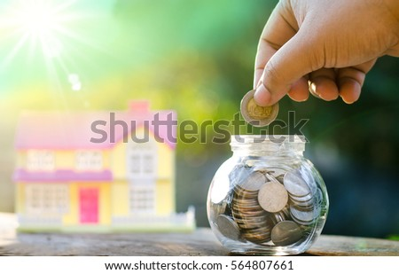 Savings money coins for house with sunlight and green background