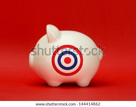 Savings on target. White piggy bank with a bulls eye target printed on it
