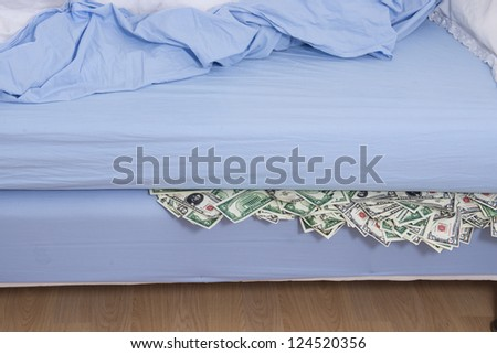 Savings or bank run concept: Hiding US dollars under the mattress