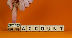 Savings or current account symbol. Businessman turns wooden cubes and changes words 'current account' to 'savings account'. Beautiful orange background, copy space. Business concept.