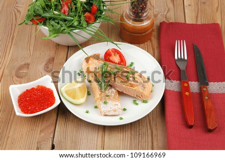 savory fish portion : roasted norwegian salmon chunks with  lemon and vegetable salad , rosemary twig and red caviar in white bowl over wooden table