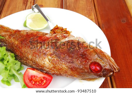 savory on wood: fried fish served with tomatoes lemon and spices