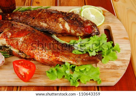 savory on wooden table: two fried fish served with tomatoes and castors