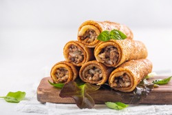 Savory pancake rolls stuffed with ground meat, rice and fried onion. White background, copy space.
