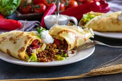 Savory pancake with minced meat and bean filling on a white plate with fork and sour cream topping on a table at home