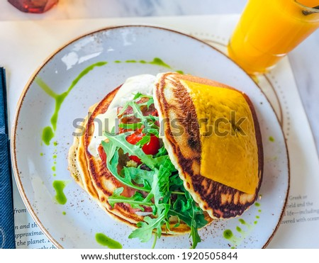 Savory pancakes with Roka salad cherry tomatoes cheddar cheese and cream cheese and pesto basil  Stok fotoğraf ©