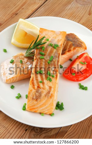 savory sea fish : baked salmon strips on white dish over wooden table