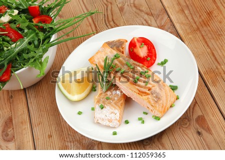 savory sea fish : baked salmon strips with vegetable salad on white dish over wooden table