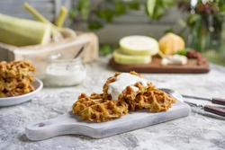 Savory squash or zucchi waffles with cheese, herbs and white sauce. Homemade baked waffles on grey textured table at kitchen, natural light, organic products on background. Selective focus, copy space