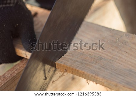saw boards with a hand saw on a tree, a saw of a tree with a hacksaw