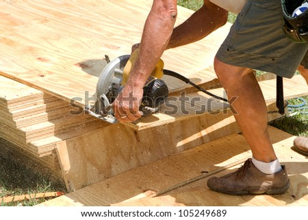 Sawdust fills the air as a carpenter uses a electric powered circular saw to cut a sheet of plywood at a construction site.