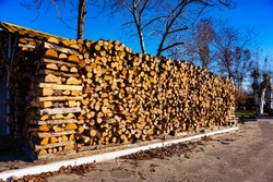 Sawed boards and logs for heating the stove, firewood is folded and lie under the open air on the street