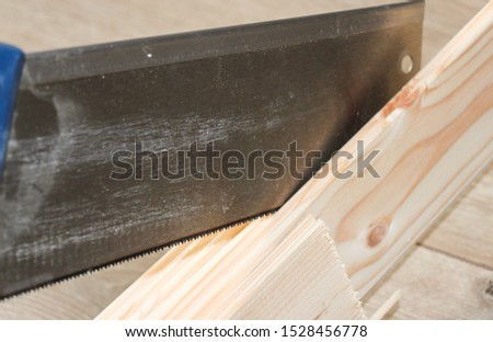 Sawing or cutting a wooden board with hand saw or hacksaw during carpentry or carpentry work #1528456778