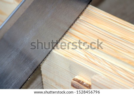 Sawing or cutting a wooden board with hand saw or hacksaw during carpentry or carpentry work #1528456796