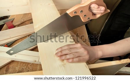 Sawing plank on a wooden background