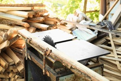 Sawmill, circular and firewood. The process of harvesting firewood. Sawing logs, boards. Circular Saw with Alder Log Pile in Background with Copy Space, Concept of Hard Work
