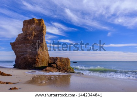 Sawtooth rock monolith stands away from the shoreline as erosion takes its toll on the red stone cliffs as waves crash on the shoreline