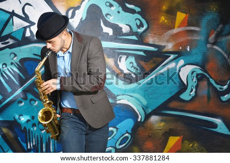 Saxophone player on graffiti wall background
