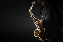 Saxophone player. Saxophonist hands playing saxophone. Alto sax player with jazz music instrument closeup