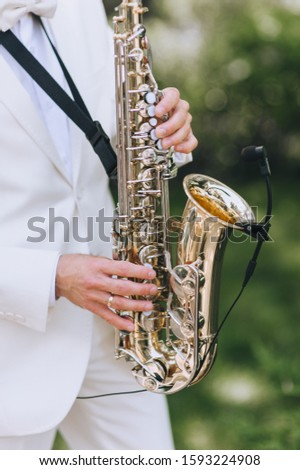 Saxophonist plays at a holiday. Hands and saxophone close-up. Beautiful instrumental music performed by a male musician on a spiritual instrument. Photography, concept.