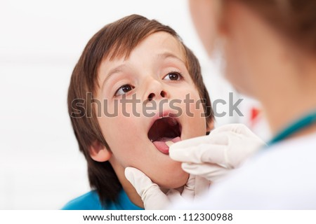 Say aaah - little boy having his throat examined by health professional - closeup