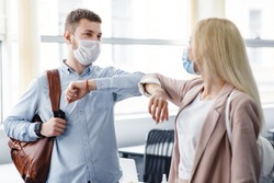 Say hello and greet, social distance and return to work after quarantine. Millennial man and woman in protective masks are touched by elbows in interior of office during COVID-19 epidemic, free space