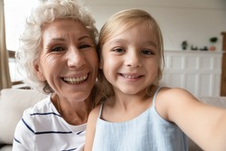 Say hi, granny! Cute little girl sitting on laps of elderly grandmother making self portrait or videocall, recording vlog, smiling preschool kid ward and older nanny looking at camera shooting video