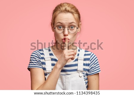 Say no more! Beautiful serious European female makes shush gesture, keeps fore finger on lips, asks to be quiet, wears casual striped t shirt and denim dungarees, says: Shh, don`t make any sound. #1134398435