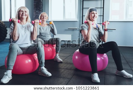 Say no to a passive lifestyle. Group of three radiant ladies focusing on an exercise while all sitting on fitness balls and lifting dumbbells during a training session.