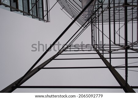 Scaffold for a building construction which has a triangle pattern shoot from bottom to up in black and white mood