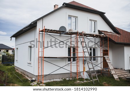 Scaffolding around the house under construction - the stage of plastering and painting the facade Photo stock ©
