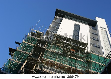 Scaffolding being removed to reveal splendid new apartment block.