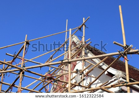 scaffolding for reconstruction the roof of building background with blue sky.