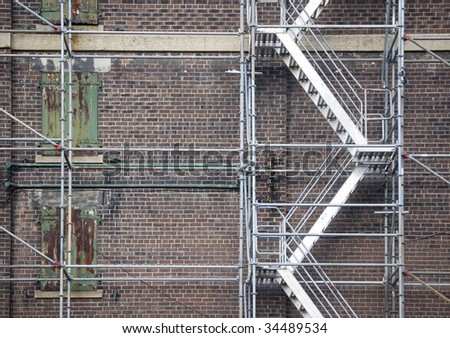 scaffolding ladder against brick wall / industrial background