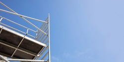 Scaffolding, metal mobile scaffold aginst blue sky background. Under construction, maintenance renovation works concept