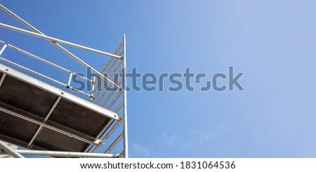 Scaffolding, metal mobile scaffold aginst blue sky background. Under construction, maintenance renovation works concept Сток-фото ©