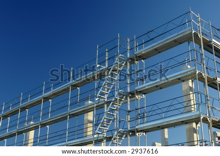 Scaffolding on a construction site, against a clear blue sky.