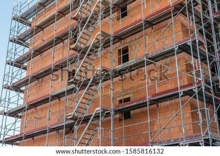 Scaffolding on a construction site, construction site and nice weather, no workers, blue sky, sunny day, scaffolding stairs