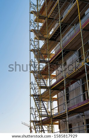 Scaffolding on a construction site, construction site and nice weather, no workers, blue sky, sunny day