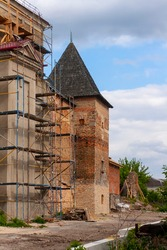 Scaffolding on the wall of an old castle. Restoration of architecture. Repair work of the monastery and castle wall. Old tower of a medieval castle with a wooden roof. Vertical photograph.
