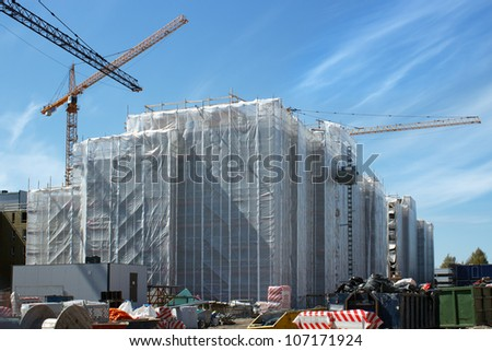 Scaffolding protected with a plastic sheet around the building in the construction site