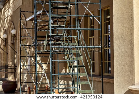 Scaffolding set up on building for renovations, repair and painting showing windows and architecture #421950124